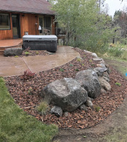 Boulders, bark and native plantings in hot tub area