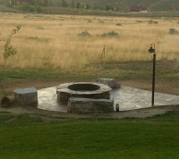 lighted fire pit area with large boulder seating